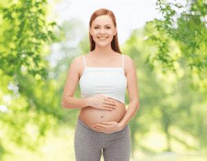 A pregnant woman smiling.