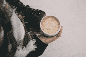 Woman holding a warm drink while standing in the snow.