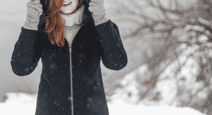 Woman bundled up in warm clothes while standing in the snow.
